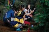 Family members pray near the cave