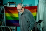 Geoffrey Ostling stands up in front of a rainbow flag in his aged care room.