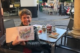 An artist displays a sketch of on a Spanish street in front of her where she is sitting at a table with a drink.