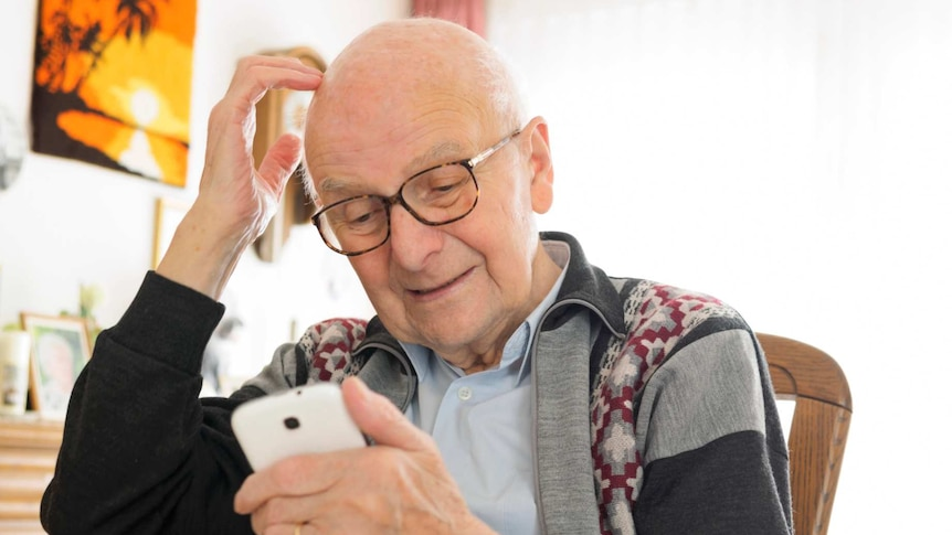 An older man scratching his head looking at a smart phone