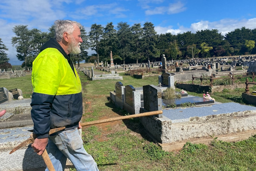 man walking through a cemetery.