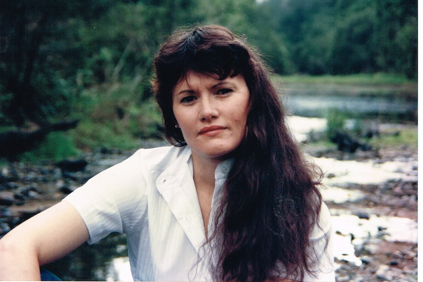 Portrait of a woman with long dark hair and white shirt sitting by a waterway