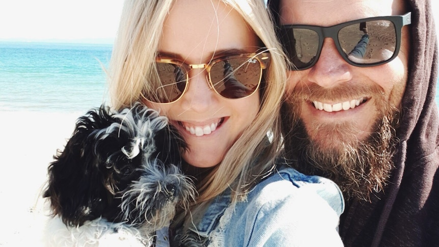 Kellie takes a selfie with Peppa and Travis on the beach to depict surviving the week with a new pet puppy.