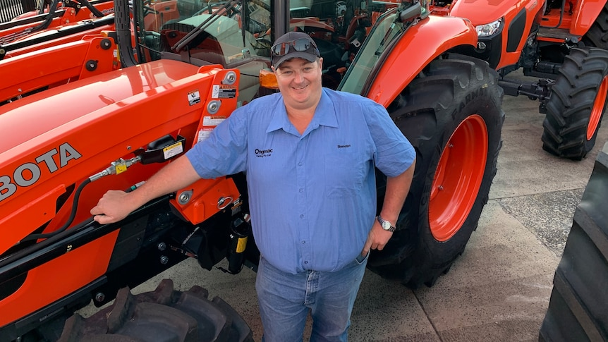 A man standing in front of red tractors smiling.