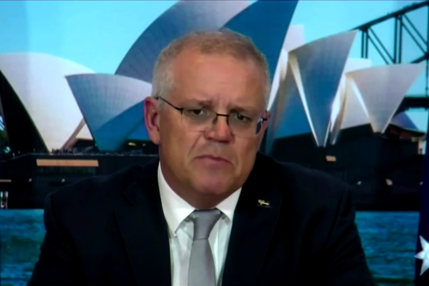 scott morrison in a suit with the australian flag and an image of the sydney opera house behind him