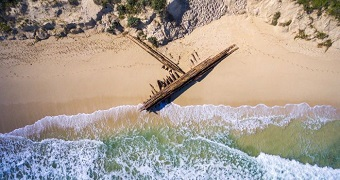 Aerial shot of shipwreck on the sand.