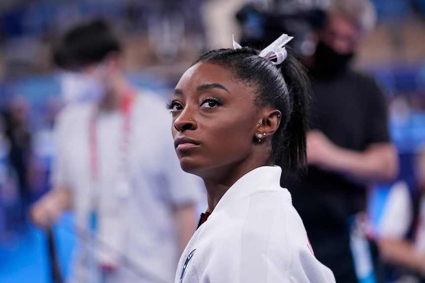 Simone Biles looks off to one side