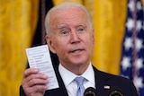 US President Joe Biden holds a note card that has the number of COVID-19-related American deaths as he speaks
