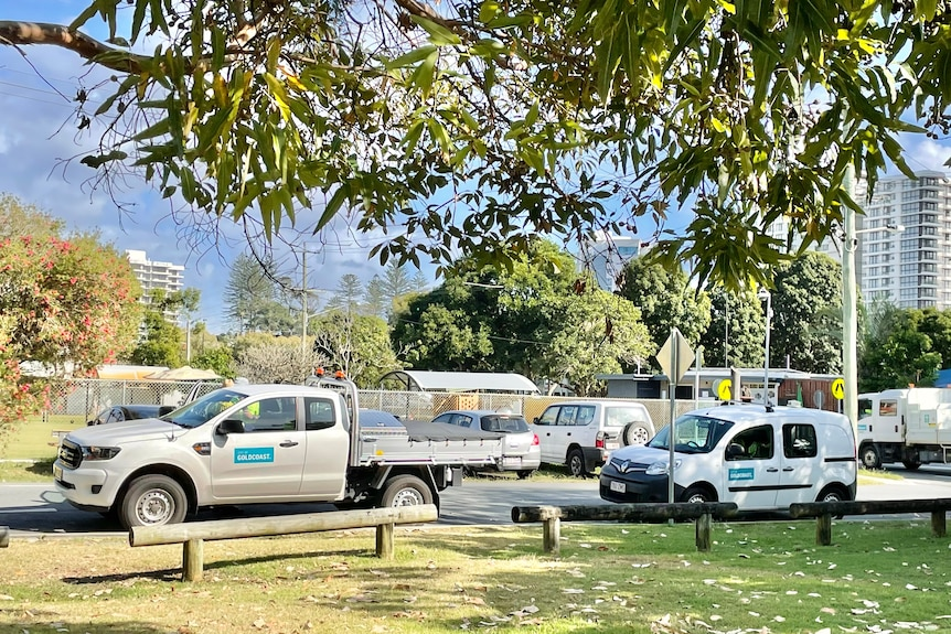 Two Gold Coast Council vehicles parked beside a park.