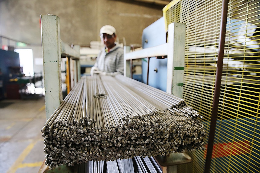 A factory worker wearing protective glasses and a cap moves steel rods at a manufacturing plant