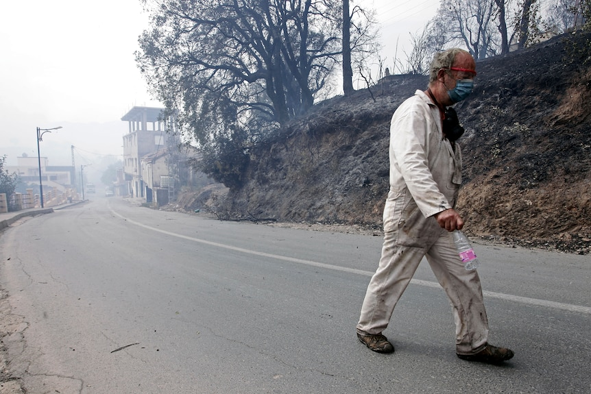 A man leaves a village near Algiers wildfires in this mountainous region.