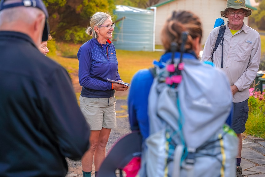 A woman wearing hiking gear and glasses stands in a circle of walkers smiling.