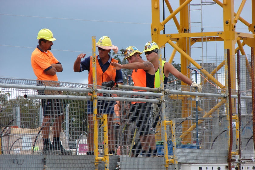 A group of men wearing high-vis clothing and hard hats stand on a worksite.