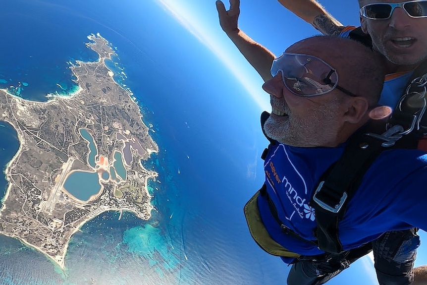 Two men skydiving over the ocean with an island underneath them.