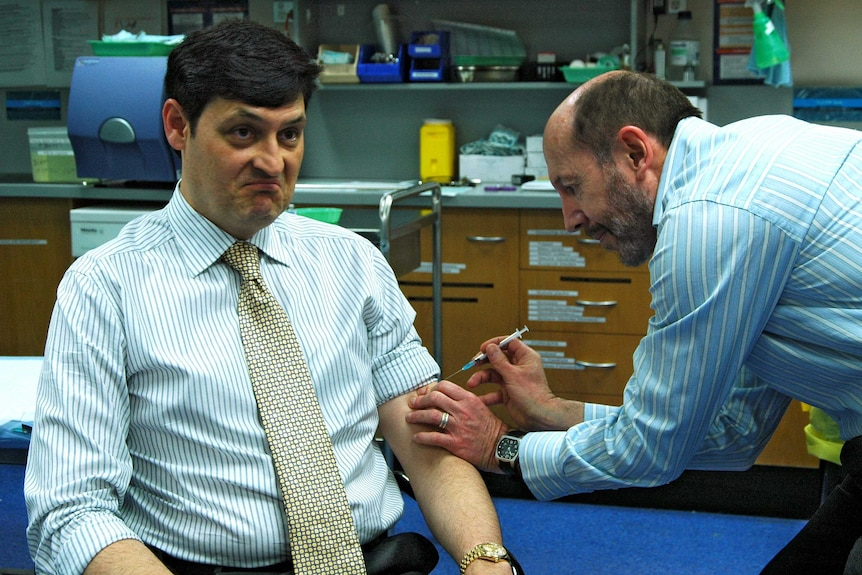 A man getting vaccinated by a doctor