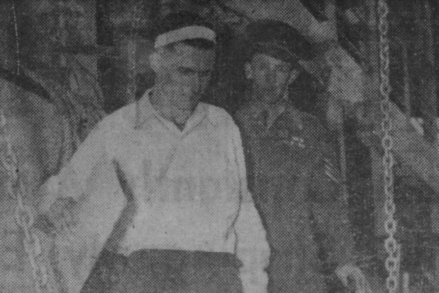 A black and white photo of a man being escorted off a boat by a man in uniform.