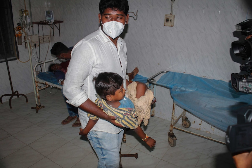 A young patient is carried by a man at the district government hospital in Eluru