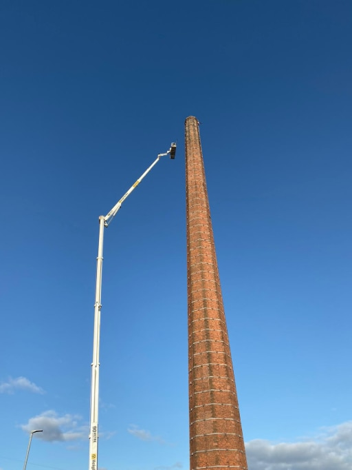 Looking up at tall brick chimney from the ground as a white cherrypicker expands to scale it against a blue sky.