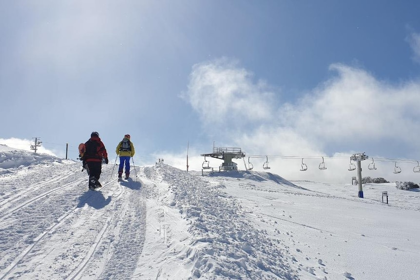 People walking through snow with blue skies over head.