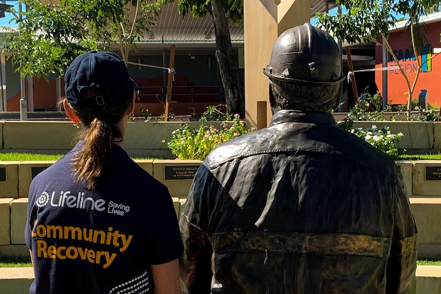 Woman in Lifeline shirt sits next to brass miner statue.