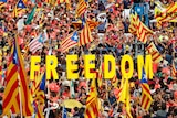 """Thousands of people wave Catalan separatist flags and hold up letters spelling out the word """"Freedom""""."""