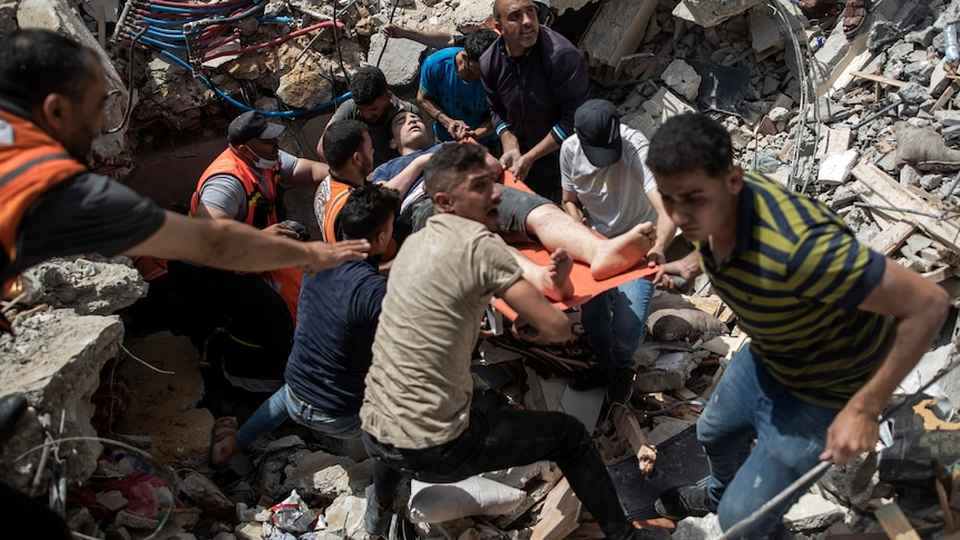 Palestinians rescue a survivor from under the rubble of a destroyed residential building
