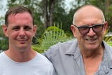 Two men, one older and with glasses, look at the camera.