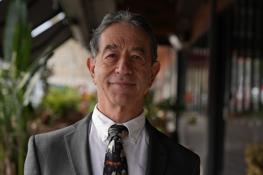 A man in a suit poses for a photo with a serious facial expression.