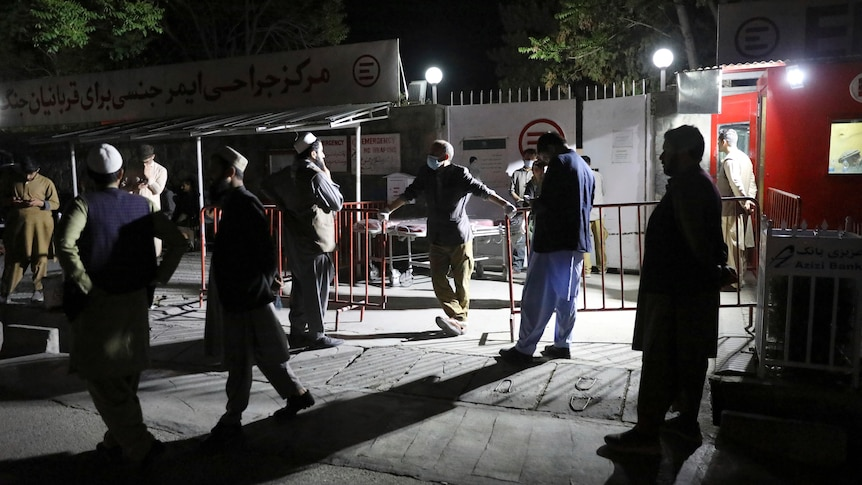 Men stand outside the gates of a hospital in the night.
