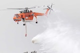 Water falls from an orange chopper into the roofs of suburban homes surrounded by trees.