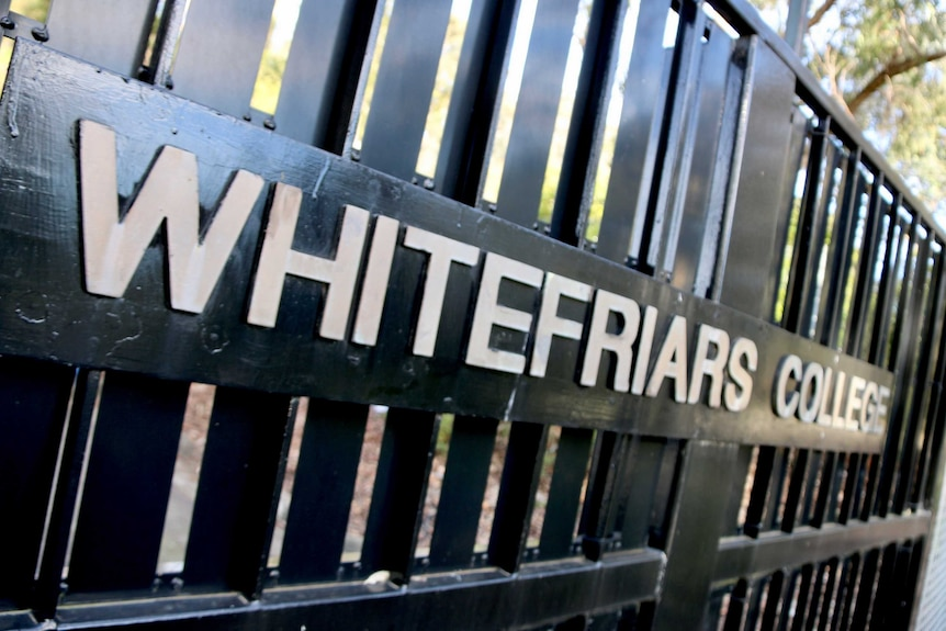 White lettering spells out 'Whitefriars College' across a closed black school gate.