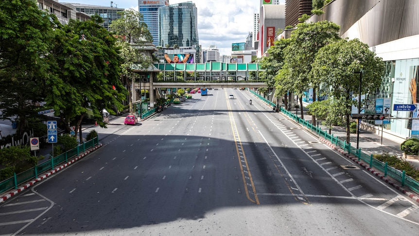 The busy Ratchaprasong intersection in Bangkok lies empty on the first day of new restrictions.