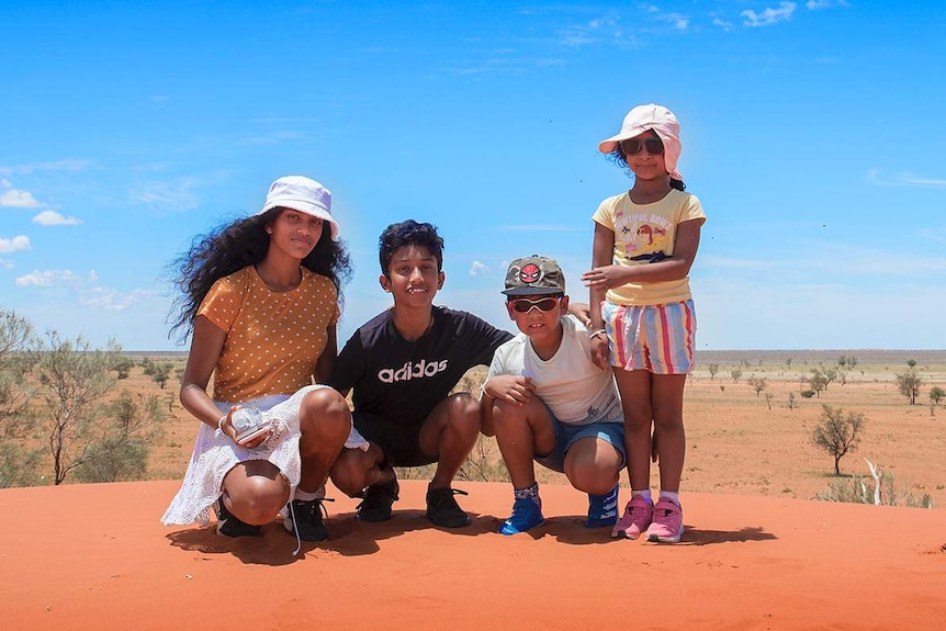Four children pose for a photo on a red sand dune.