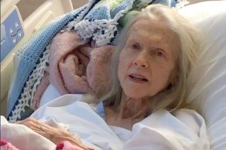 An elderly woman lays on Queensland Health linen, looking frail, grey hair.