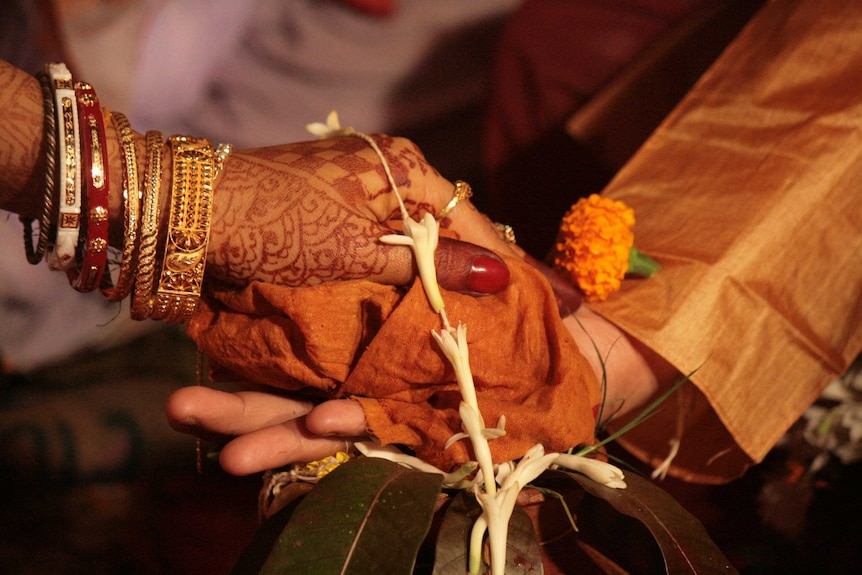 A woman's hand, covered in henna and her arm adorned with bangles, rests on top of a man's hand.