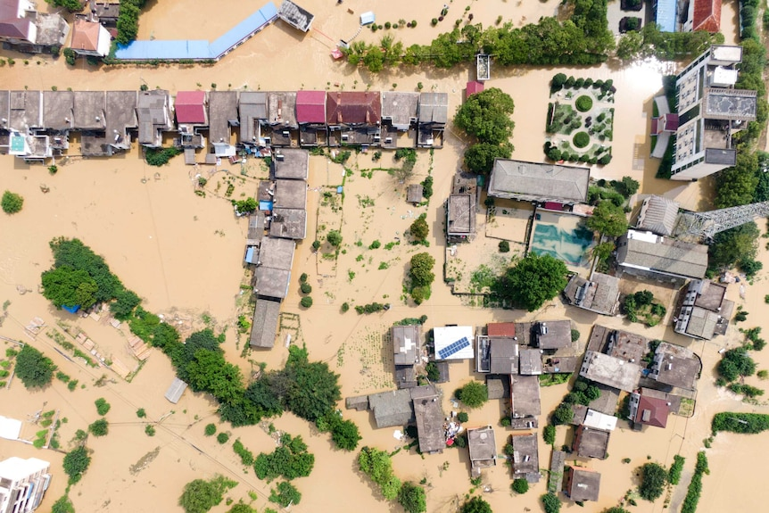 An aerial photo of a village which has been inundated with brown floodwaters.