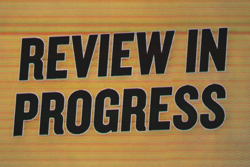 """A sign in big black type on a yellow background on an electronic scoreboard shows the words """"Review in progress""""."""