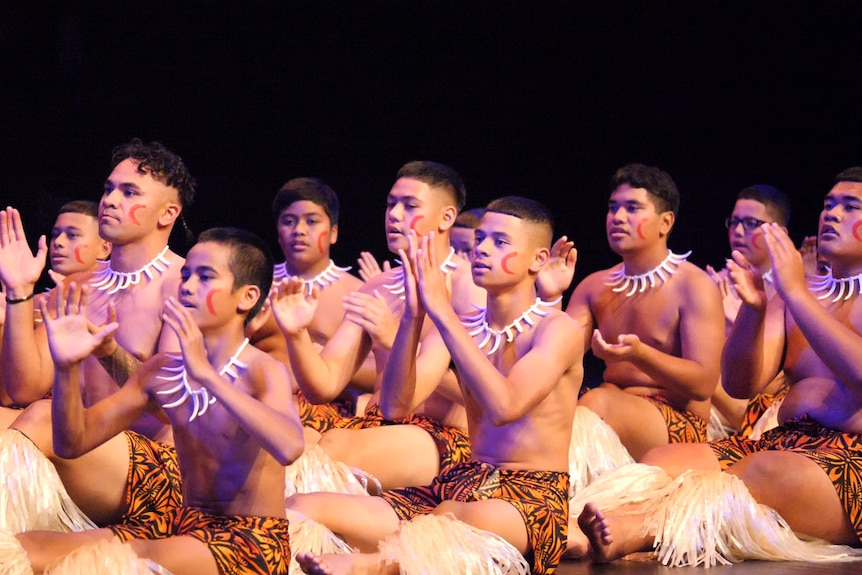 Young, shirtless boys wearing traditional Samoan necklace and sarongs, with painted faces