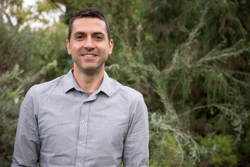 Man in grey shirt stands in front of greenery, smiling