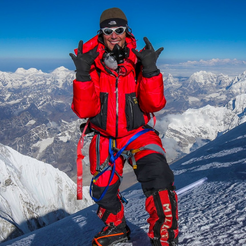 A man in a red snow suit standing on a snowy peak