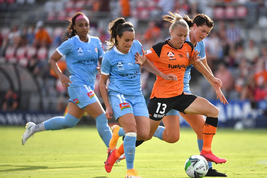 Women wearing blue and orange football uniforms tussle over a soccer ball.