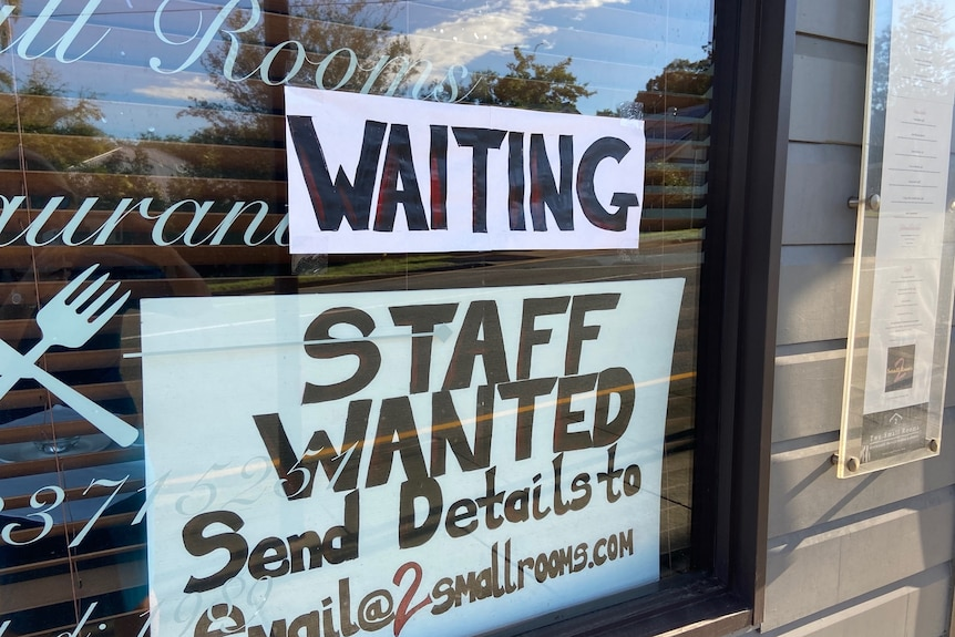 A sign saying 'staff wanted' in the window of a restaurant.