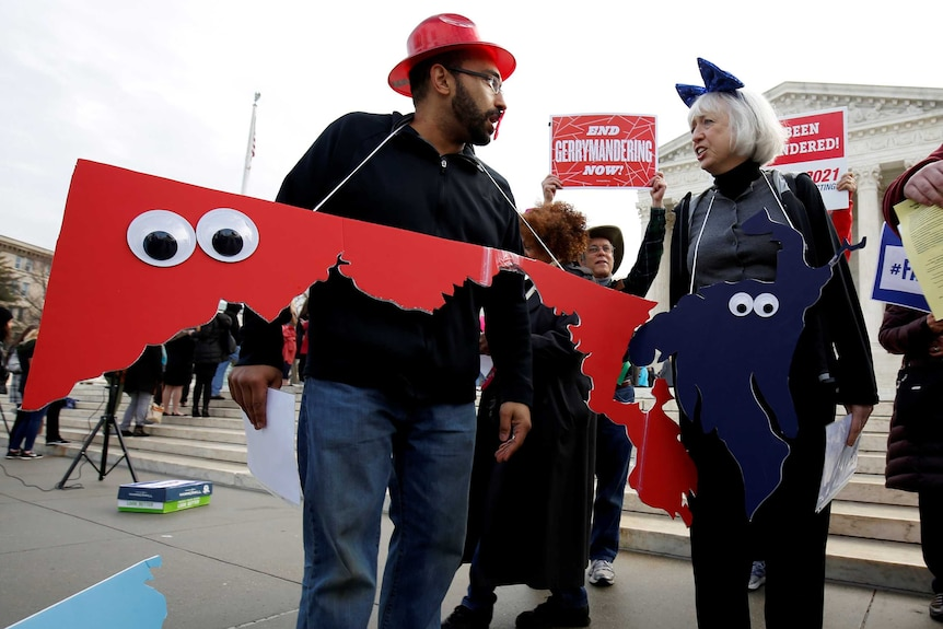 Protesters with congressional district cut-outs around their necks