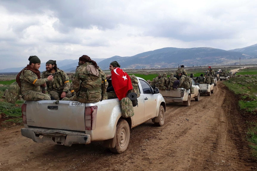 A line of trucks carrying soldiers moves down a dirt road.
