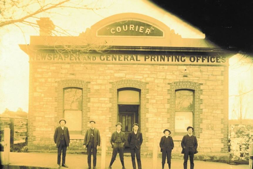 """An old, yellowed photo of a group of men standing outside a brick building with a sign that reads """"COURIER""""."""