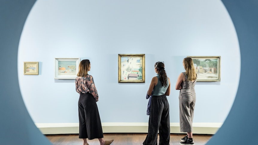 Three young women stand in front of a series of Clarice Beckett paintings in an exhibition