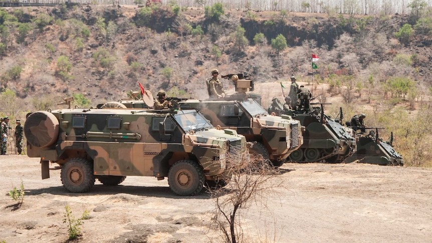 Several military personnel carriers line up in the desert.
