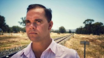 A man stands next to railway tracks, looking into the distance.