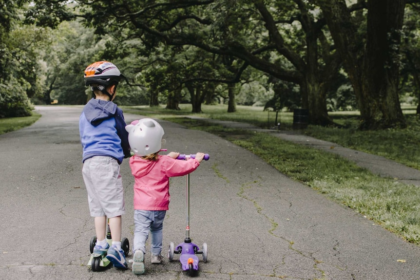 Two kids on scooters in a green park