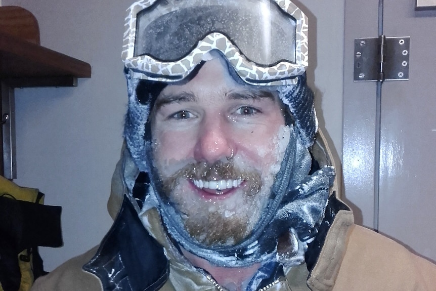A man with skiing googles on his forehead and a frozen beard smiles for a story on working as a plumber in Antarctica